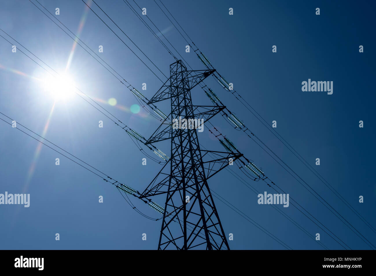 electricity pylon with lens flare - Stock Image
