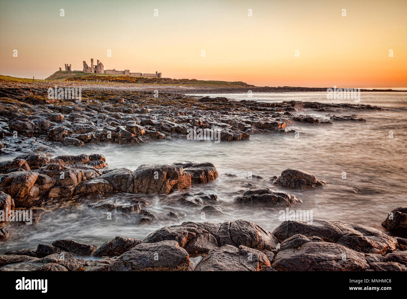 Sunrise at Dunstanburgh Castle on the Northumberland coast, North East England. - Stock Image