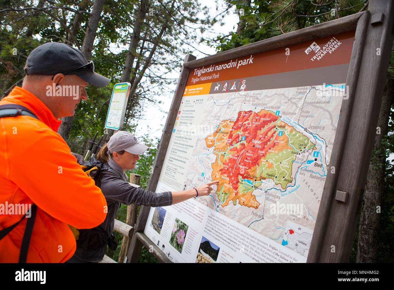 Ranger of Triglav National Park pointing at map of area whilst guiding tourist around Krn mountain in southwestern Julian Alps in northwestern Slovenia - Stock Image
