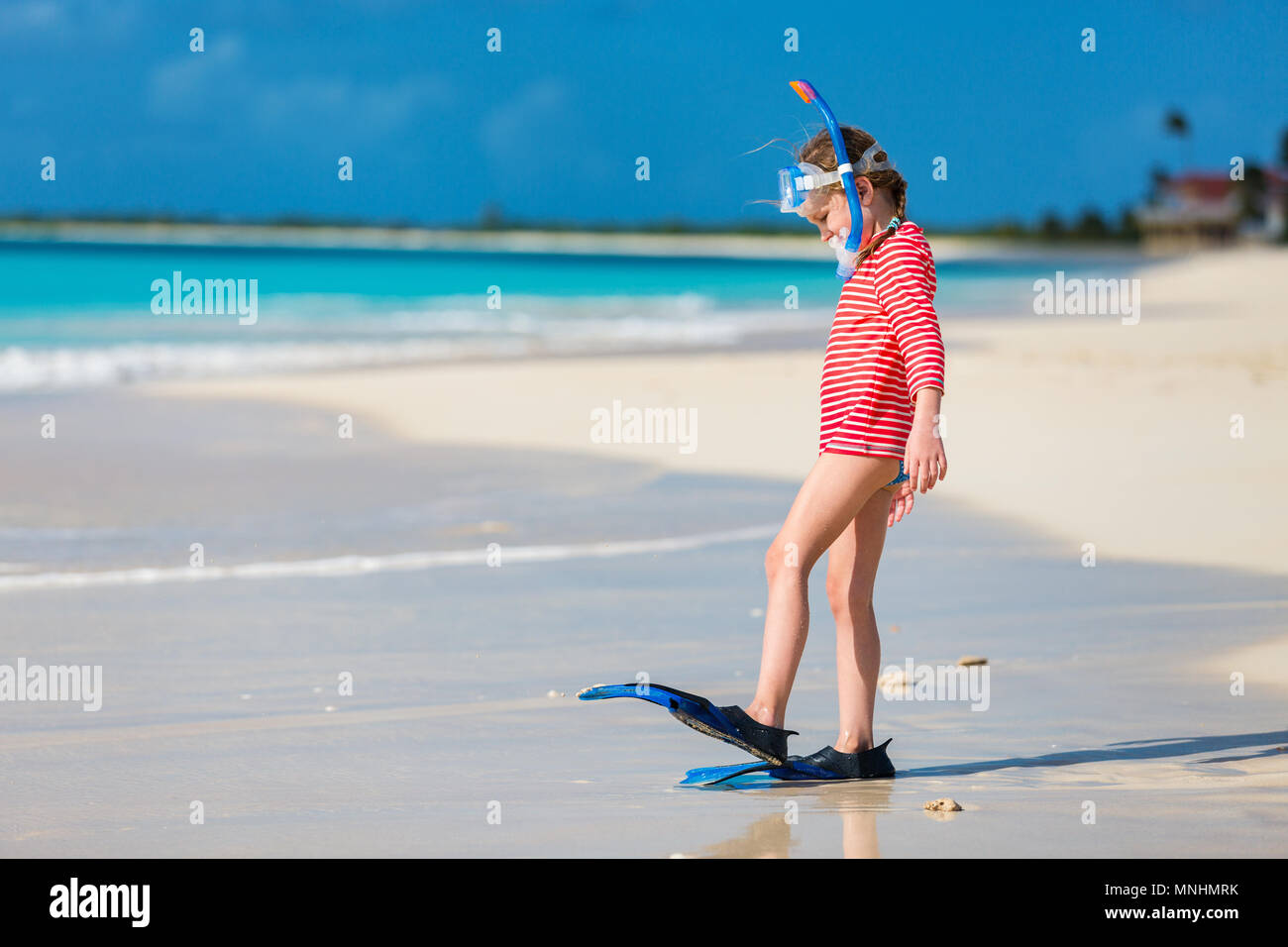 Adorable little girl with snorkeling equipment at beach during summer vacation - Stock Image