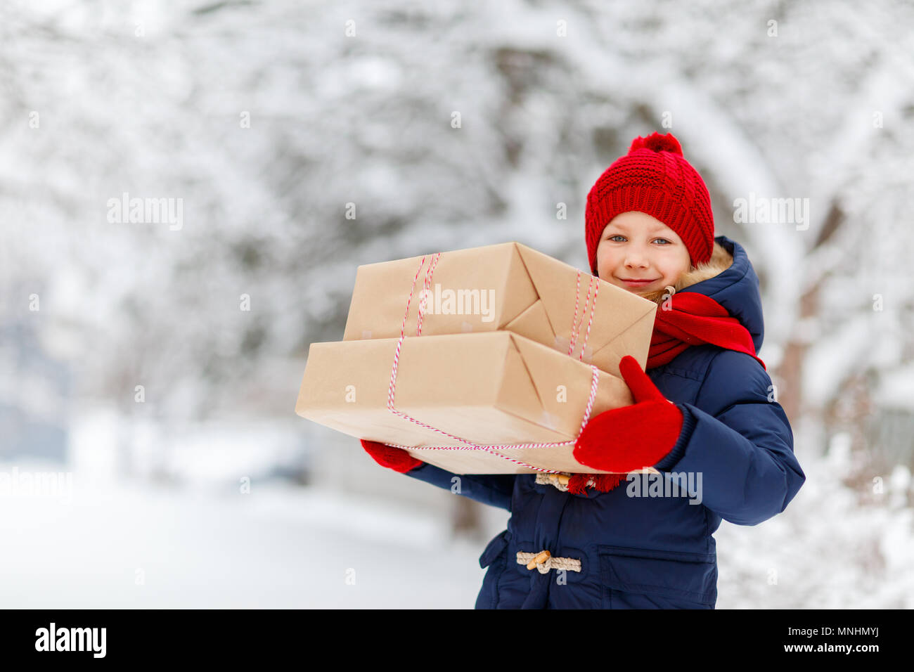 Adorable little girl wearing warm clothes outdoors on Christmas day holding gifts - Stock Image
