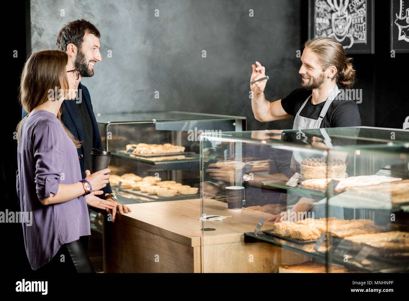 Young couple buying coffee standing with handsome barista in the modern coffee shop - Stock Image