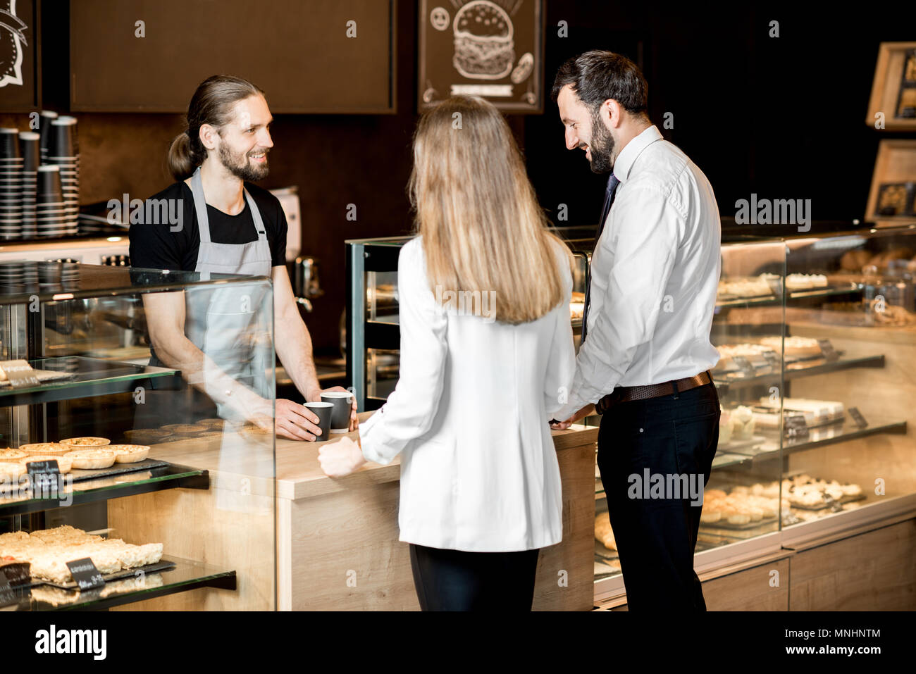 Young business couple buying coffee standing with handsome barista in the modern coffee shop - Stock Image