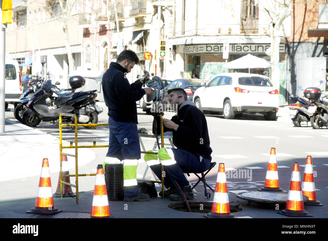 TECHNICIANS INSTALLING OPTIC FIBER - Stock Image