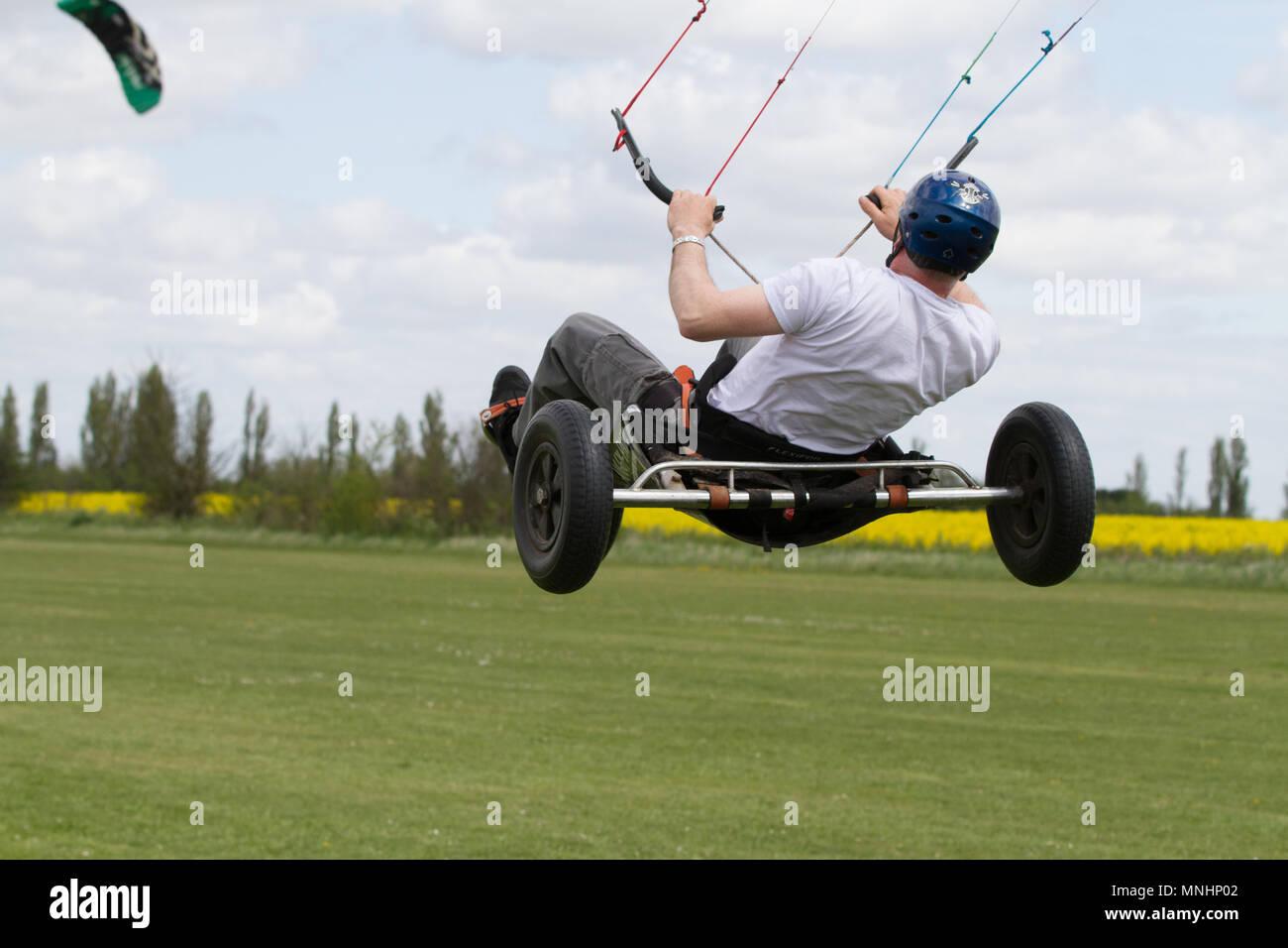 Extreme sport kite landboarding in Essex, UK. Airborne in a land buggy.. - Stock Image