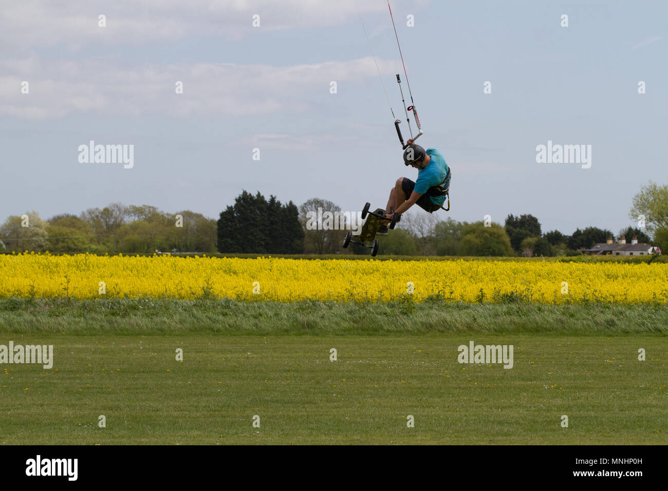 Extreme sport kite landboarding in Essex, UK. Airborne over a field. - Stock Image