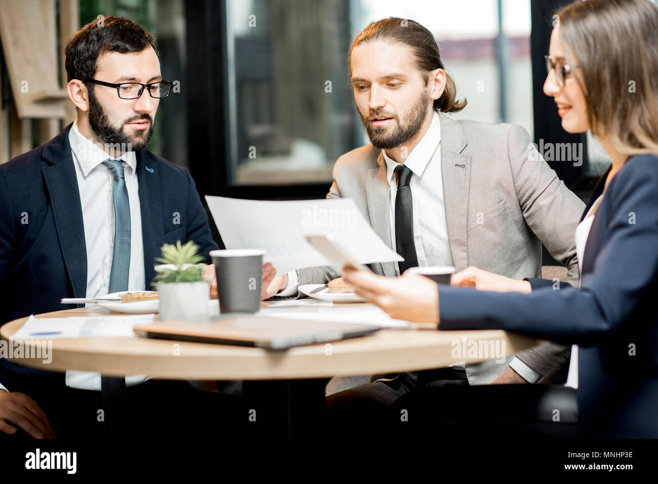 Three business people working with documents sitting together during the coffee break in the modern cafe interior - Stock Image