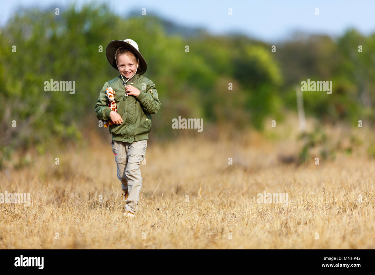 0c67adaa58 Adorable little girl in South Africa safari running in a bush with giraffe  toy - Stock