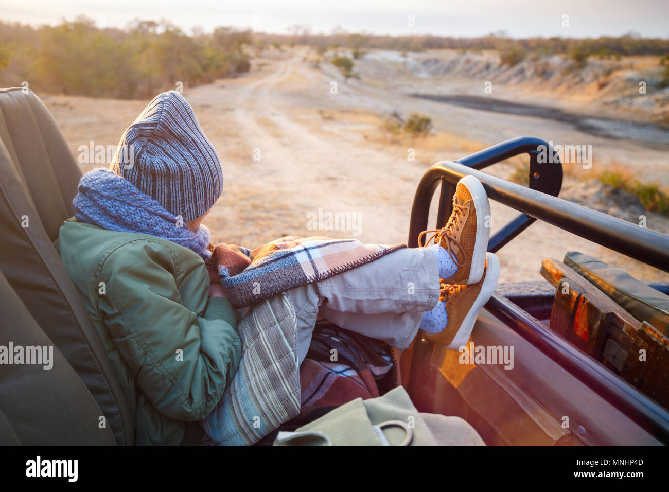 Adorable little girl wearing warm clothes outdoors on beautiful winter morning safari game drive - Stock Image