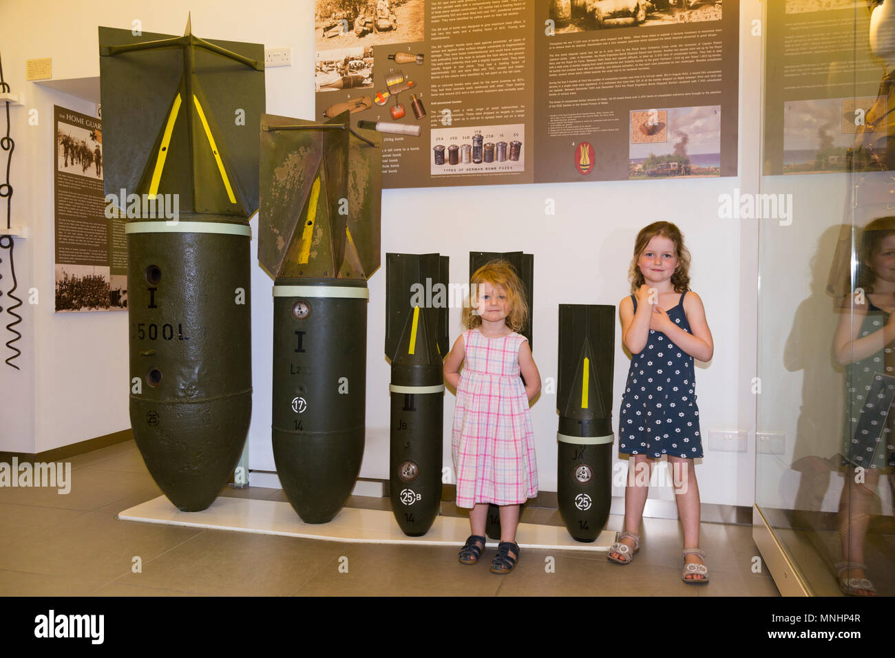 Display of bombs of various sizes used by axis countries Germany & Italy against Malta during World War II. Accompanied by young children child kid kids at the Malta at War Museum in Malta - Stock Image