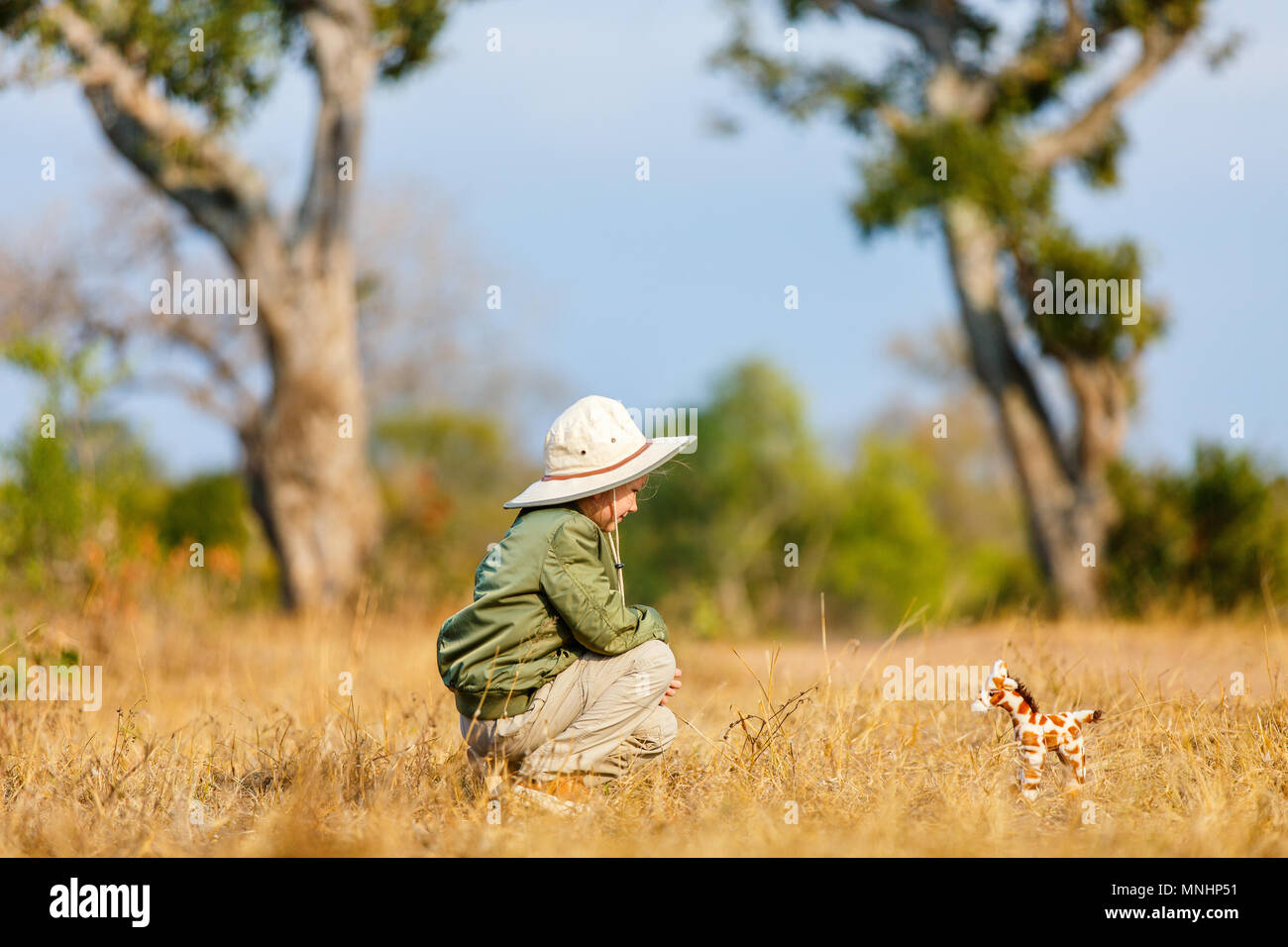 Adorable little girl in South Africa safari with giraffe toy - Stock Image