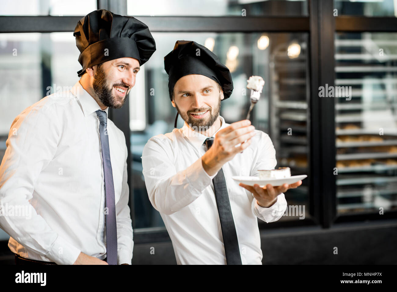 Two elegant confectioners or chef cooks checking the quality of the delicious cake in the bakery office - Stock Image