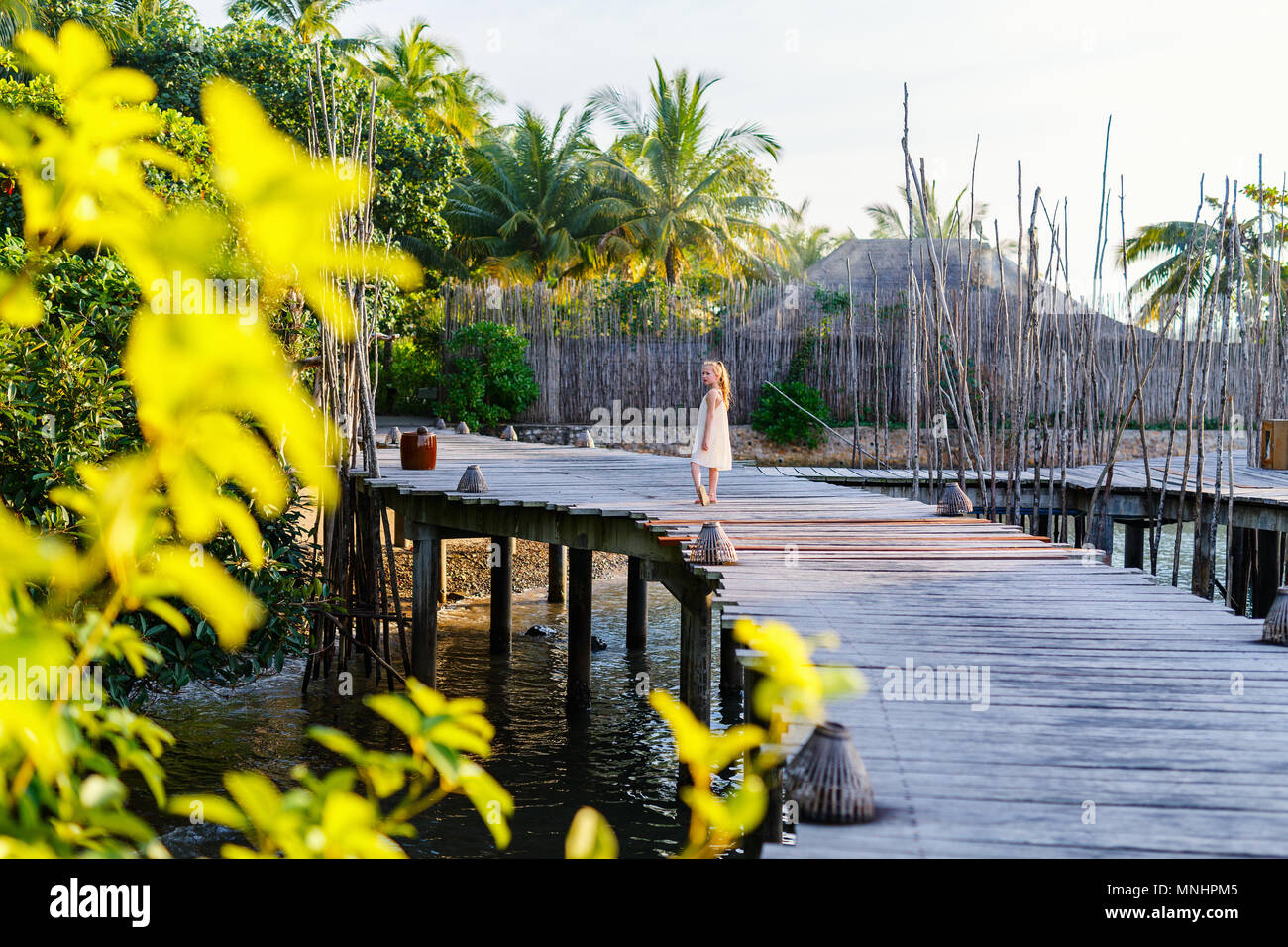 Little girl walking on wooden footbridge during summer vacation at luxury resort - Stock Image