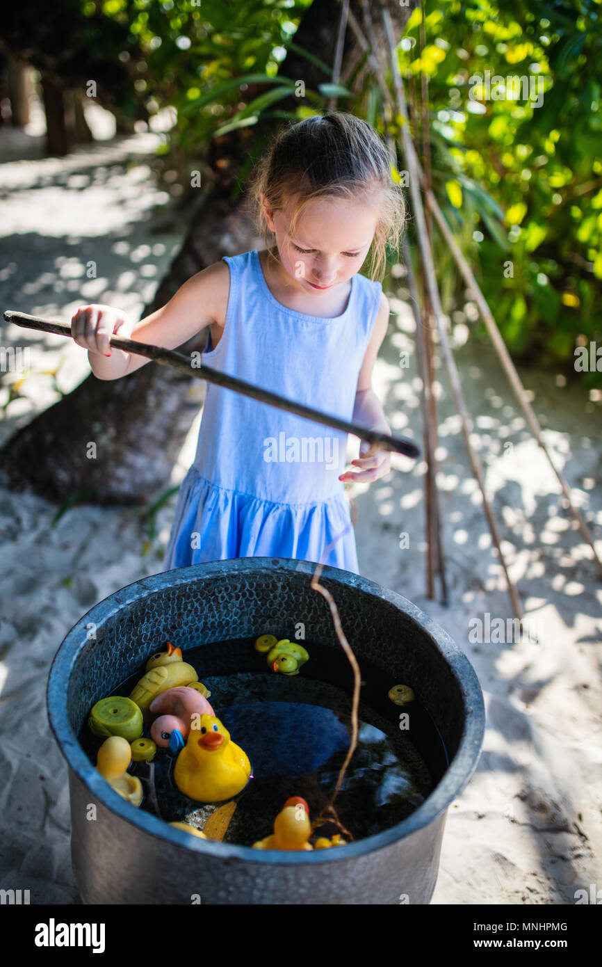 Casual portrait of little girl playing outdoors on summer day - Stock Image