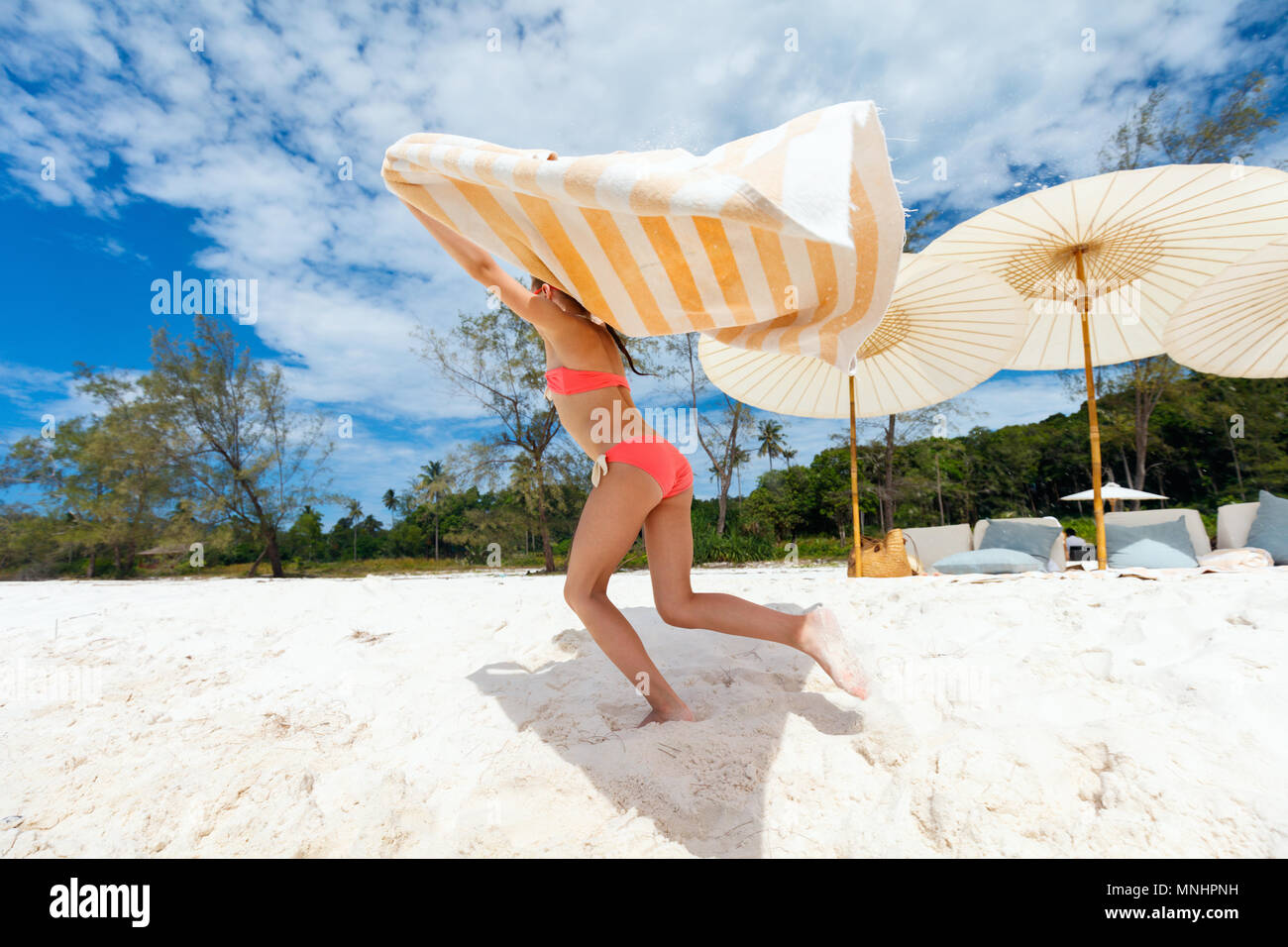 Cute little girl having fun running with towel and enjoying vacation on tropical beach with white sand and turquoise ocean water - Stock Image