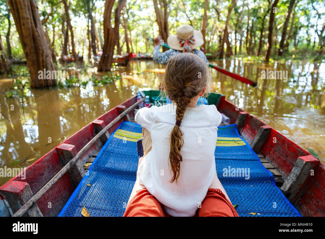 Back view of a little girl have a boat ride at flooded forest in Cambodia - Stock Image