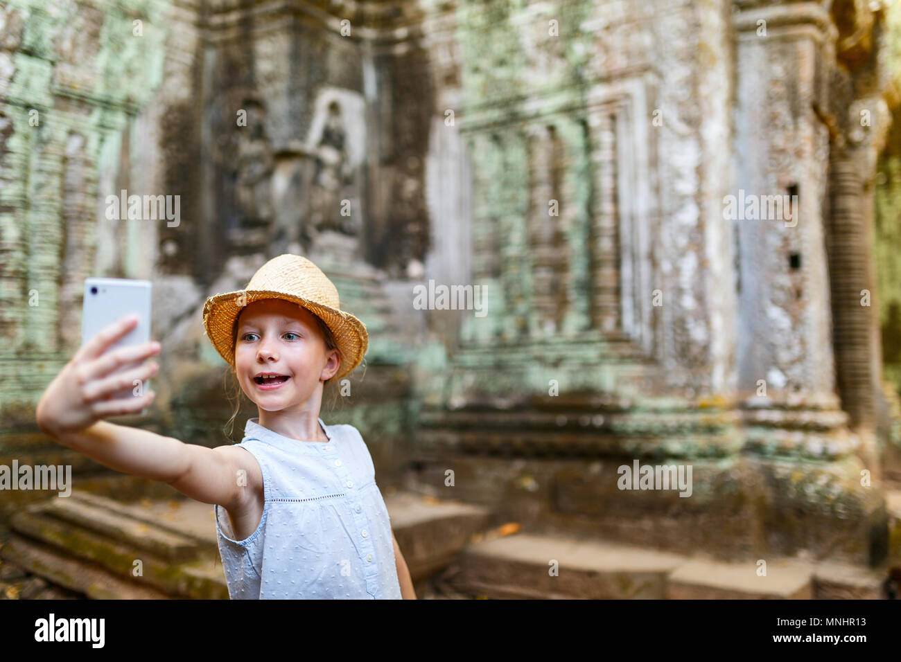 Little girl in ancient Angkor Wat temple in Siem Reap,  Cambodia - Stock Image