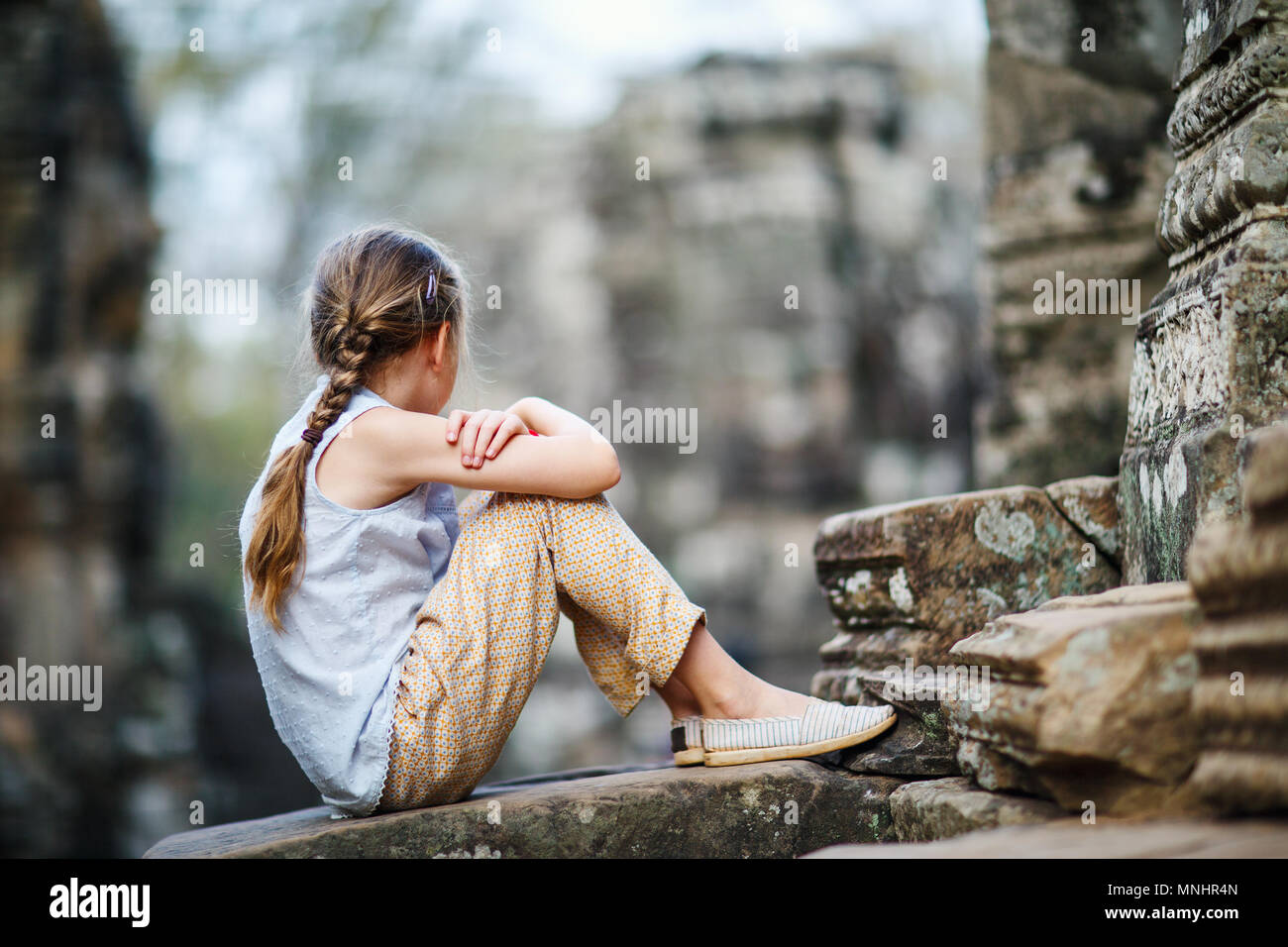 Little girl at ancient Preah Khan temple in Angkor Archaeological area in Cambodia - Stock Image