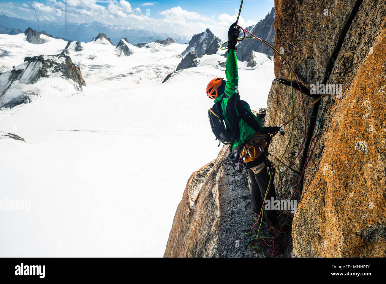 Side view of adventurous rock climber preparing to rappel from climbing route, Aiguille Du Midi, Haute-Savoie, France - Stock Image