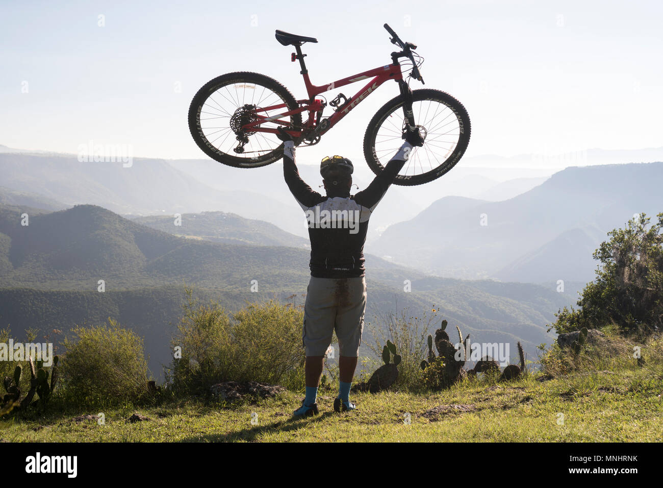 Rear view of man holding aloft mountain bike in natural setting with mountains in background, Pena del Aire, Huasca de Ocampo, Hidalgo, Mexico - Stock Image