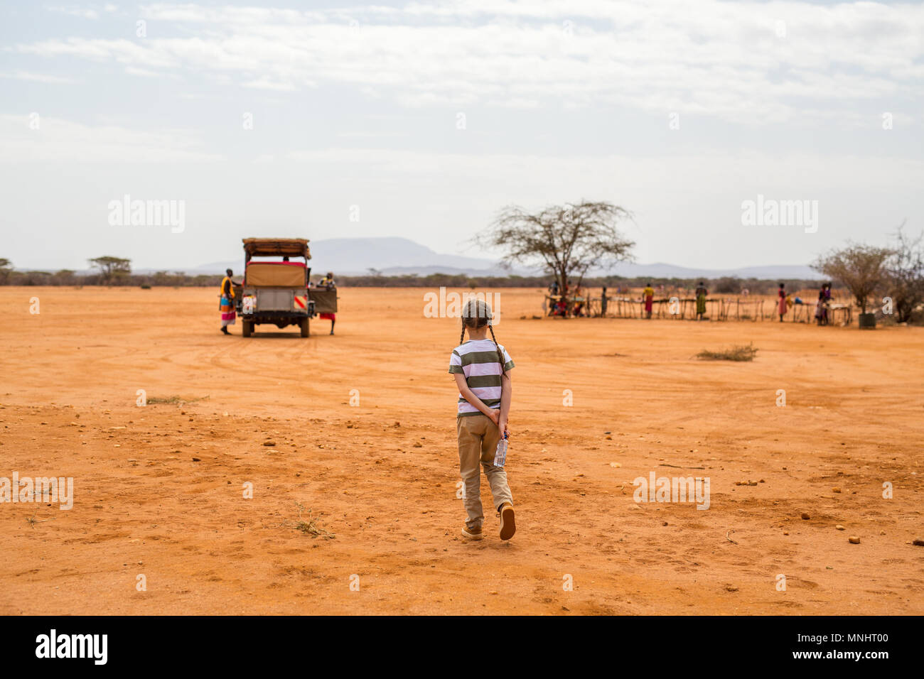 Adorable little girl in Kenya safari walking towards open vehicle - Stock Image