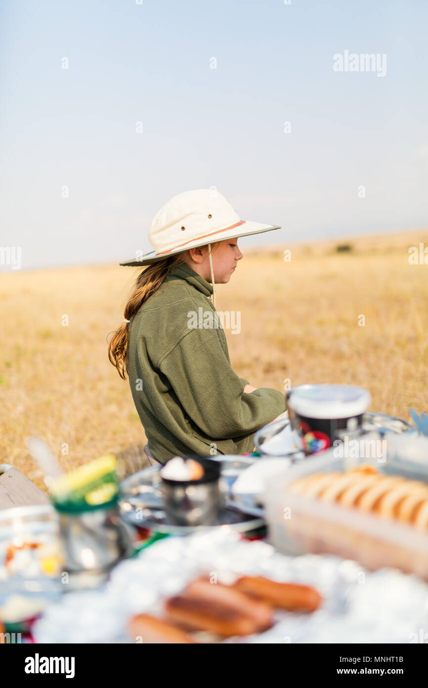 Adorable little girl in Kenya safari enjoying bush breakfast - Stock Image