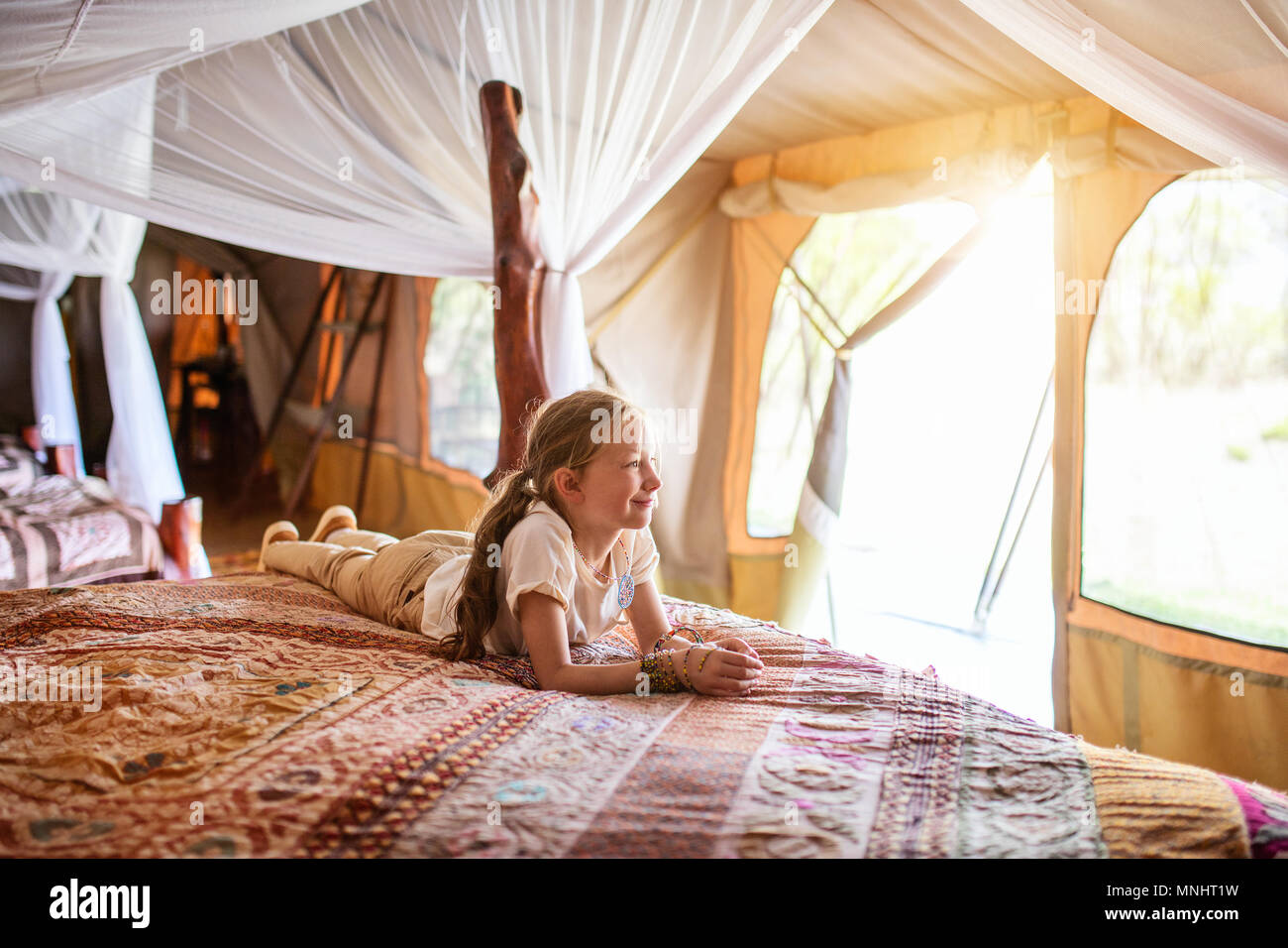 Little girl in safari tent enjoying vacation in Africa - Stock Image