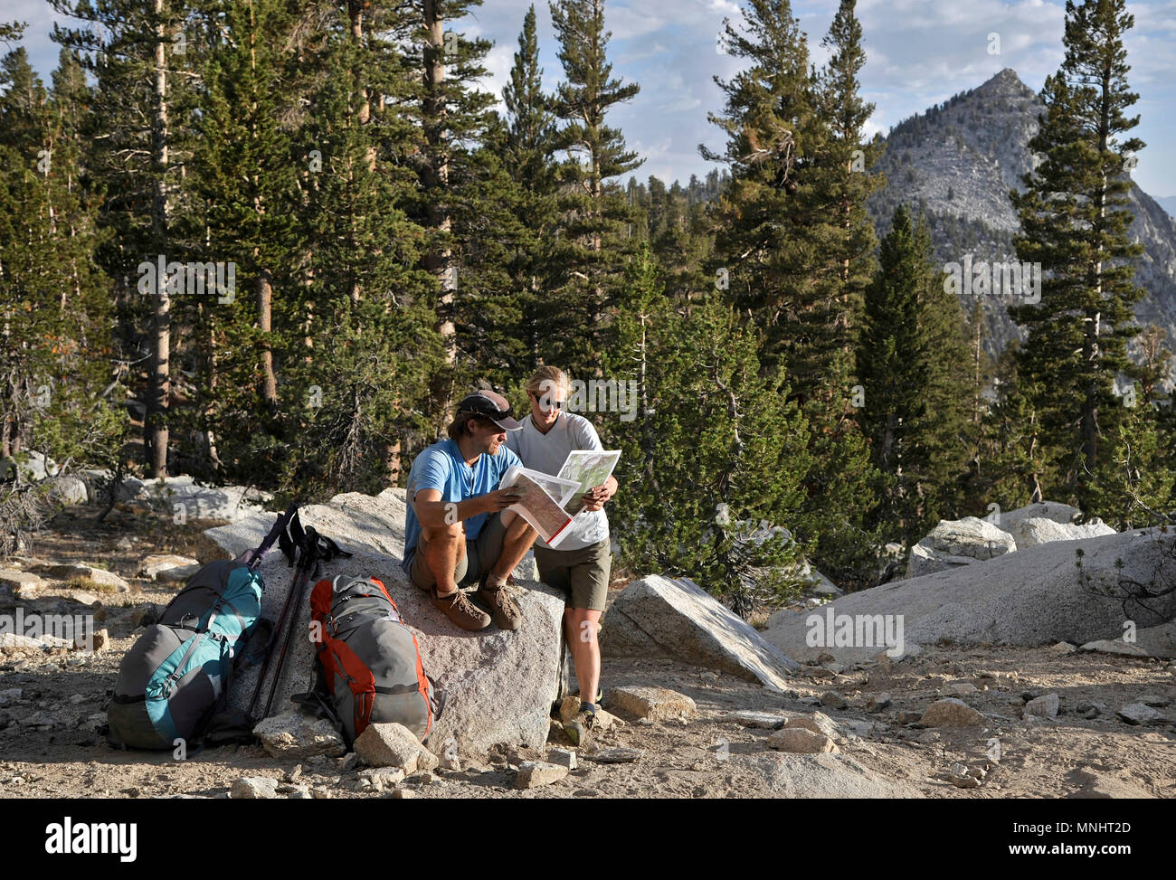 Backpackers refer to their map on the Copper Creek Trail on a two-week trek of the Sierra High Route in Kings Canyon National Park in California. The 200-mile route roughly parallels the popular John Muir Trail through the Sierra Nevada Range of California from Kings Canyon National Park to Yosemite National Park. - Stock Image