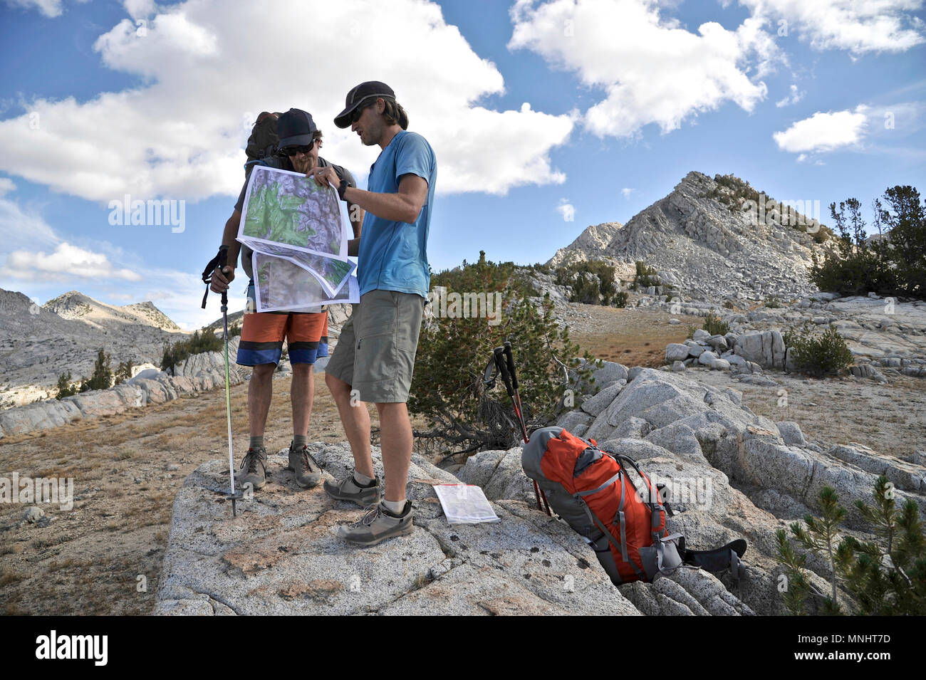 Backpackers refer to their map at Grouse Lake Pass on a two-week trek of the Sierra High Route in Kings Canyon National Park in California. The 200-mile route roughly parallels the popular John Muir Trail through the Sierra Nevada Range of California from Kings Canyon National Park to Yosemite National Park. - Stock Image