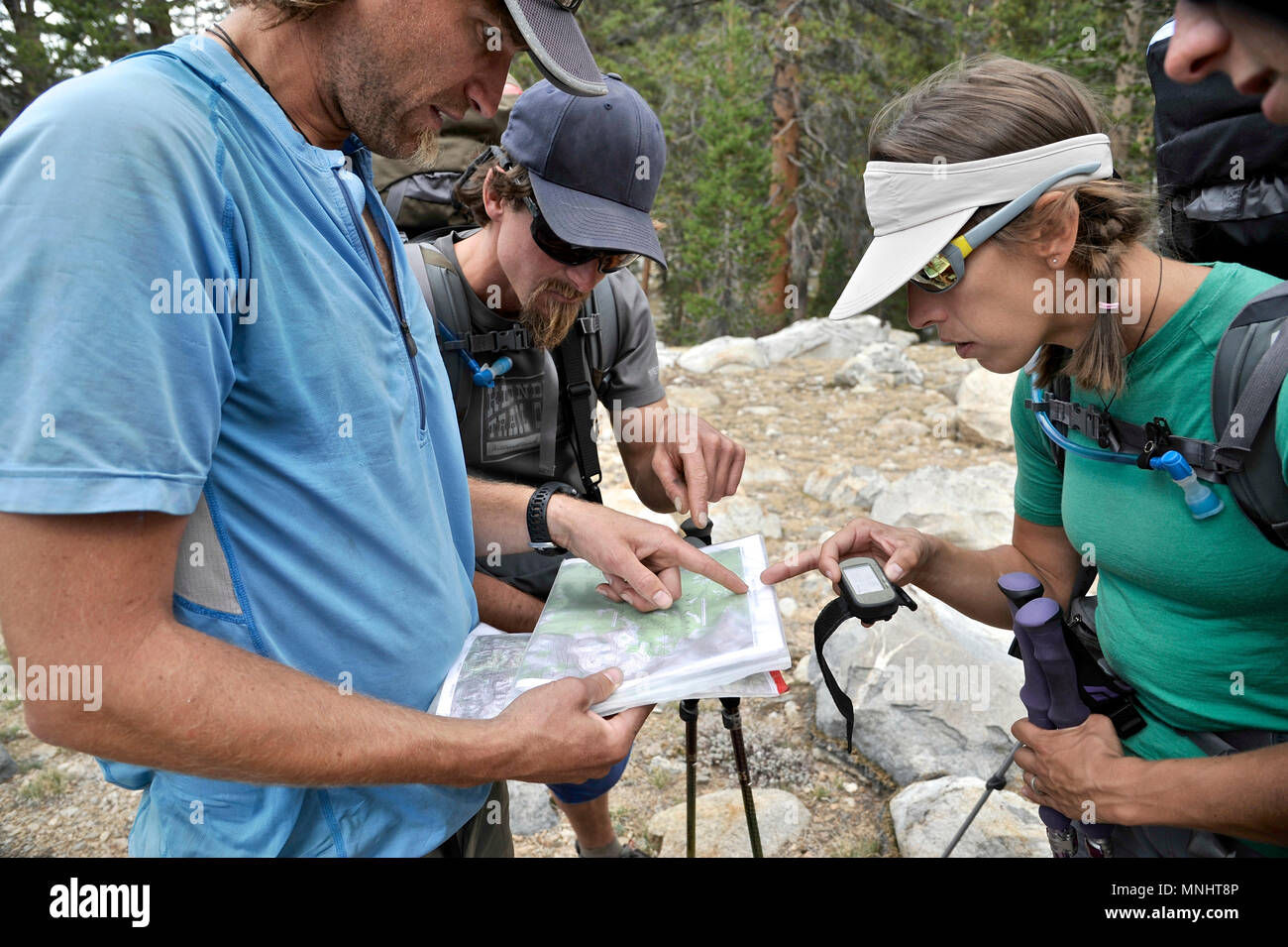 Backpackers refer to their maps in Glacier Valley on a two-week trek of the Sierra High Route in Kings Canyon National Park in California. The 200-mile route roughly parallels the popular John Muir Trail through the Sierra Nevada Range of California from Kings Canyon National Park to Yosemite National Park. - Stock Image