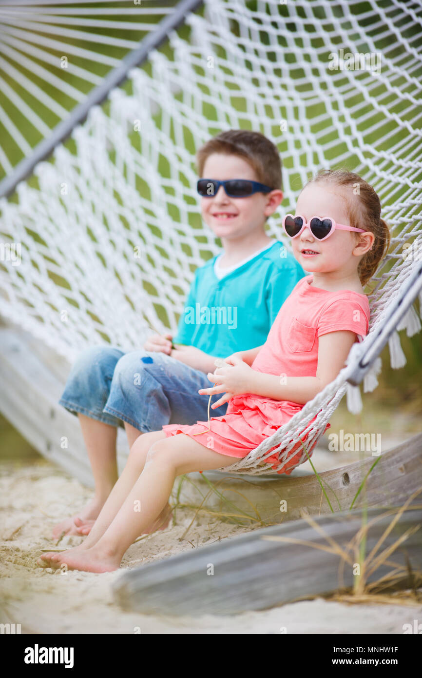 Brother and sister sitting in hammock - Stock Image