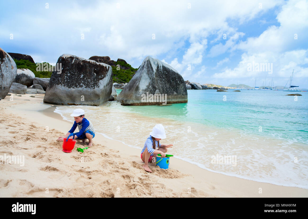 Kids wearing sun protection rash guard at beach during summer vacation - Stock Image