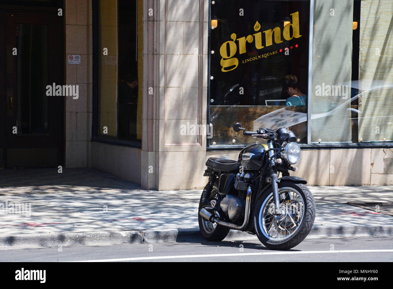 A Black Triumph Motorcycle Parked Outside Of Local Coffee Shop In Chicagos Lincoln Square Neighborhood