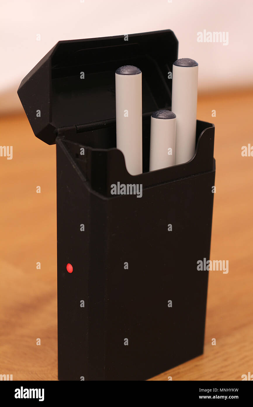 Electronic cigarette batteries charging in a case style charger - Stock Image