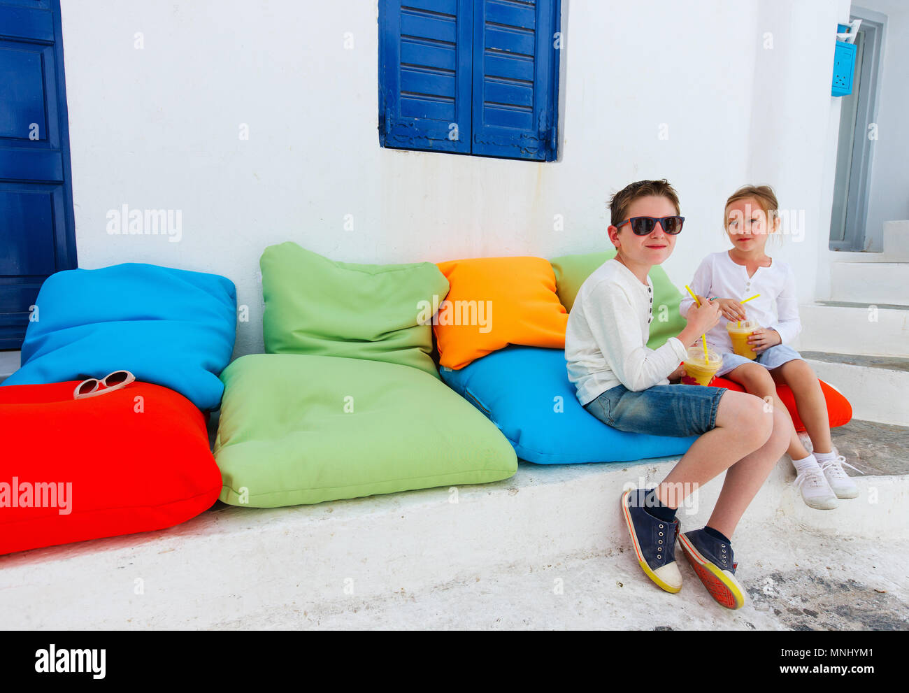 Two cute kids brother and sister drinking fresh smoothies on a colorful pillows at outdoor cafe on summer day - Stock Image