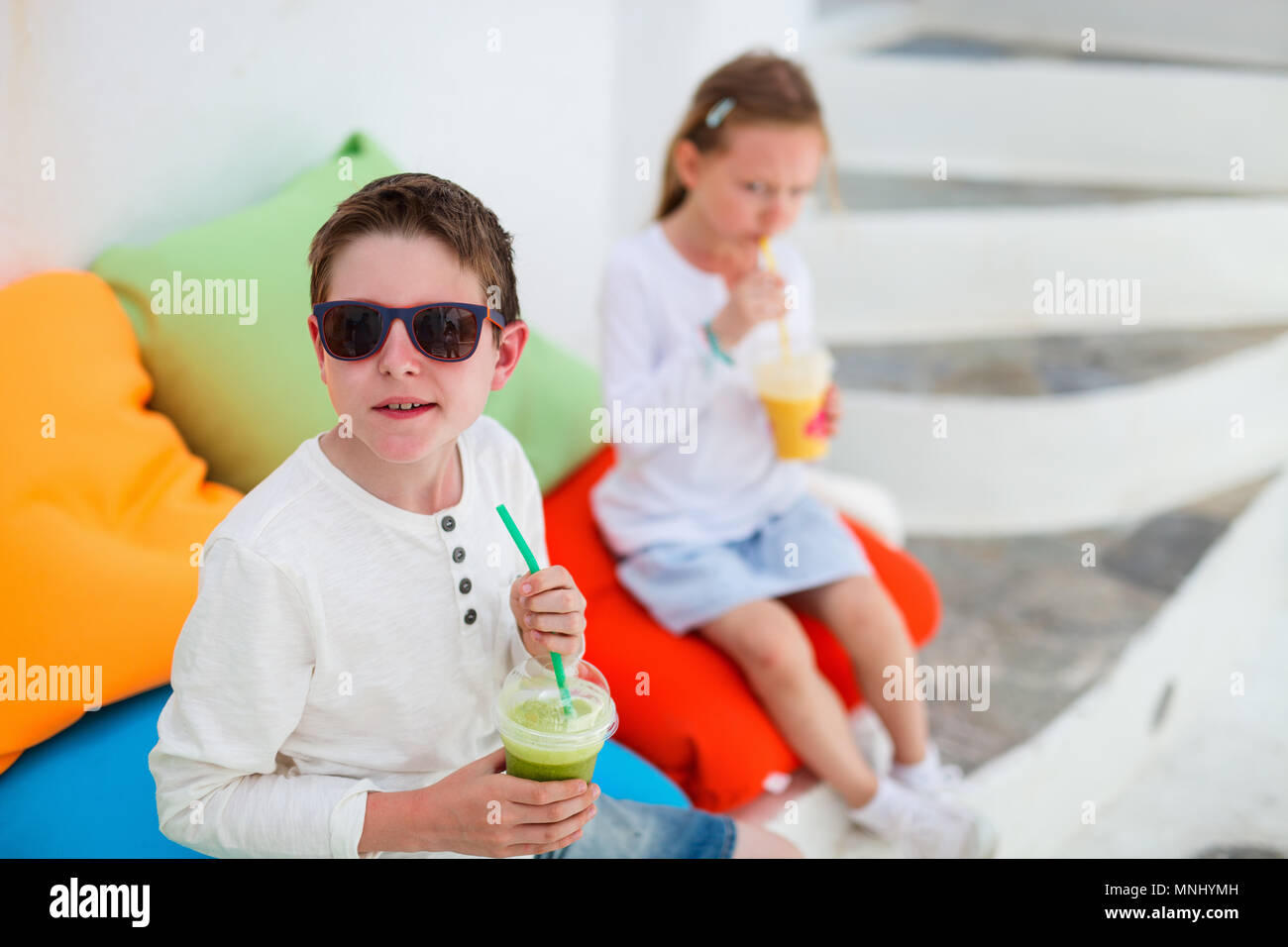 Two cute kids brother and sister drinking fresh smoothies on a colorful pillows at outdoor cafe on summer day Stock Photo