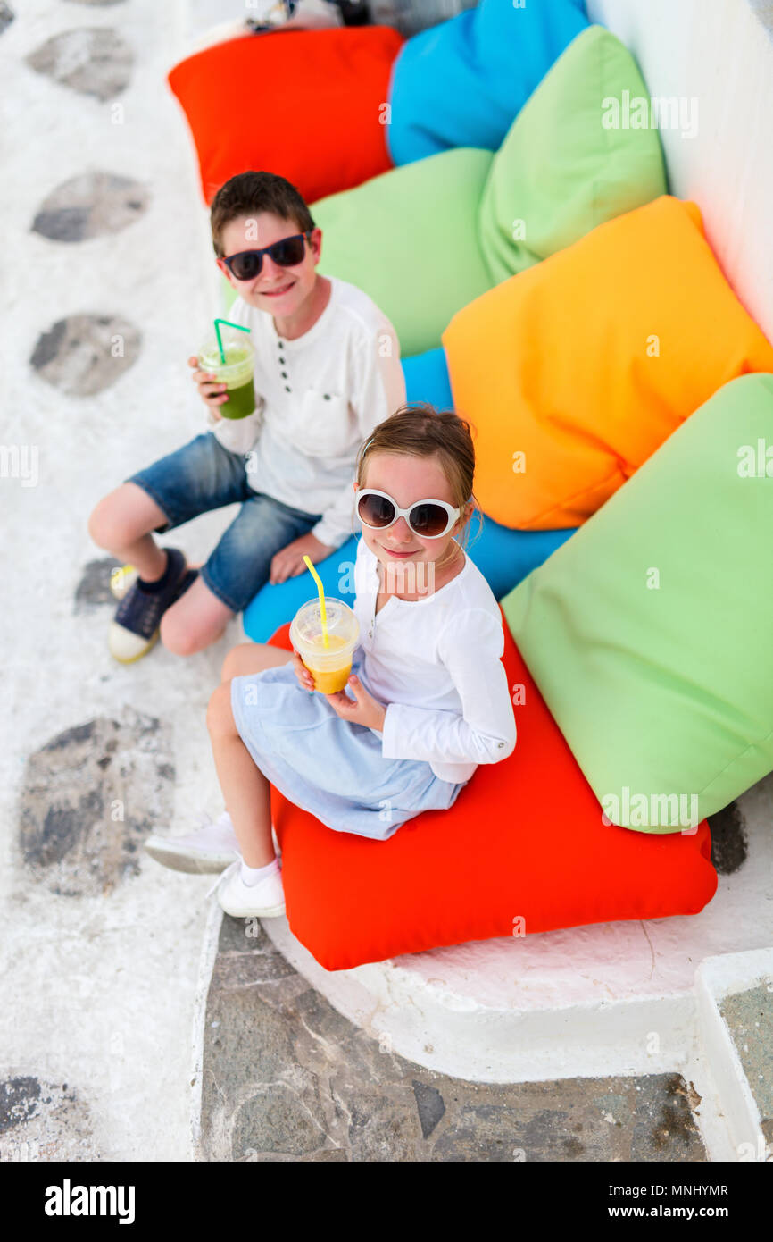 Two kids relaxing on a colorful pillows at outdoor cafe on street of traditional greek village - Stock Image