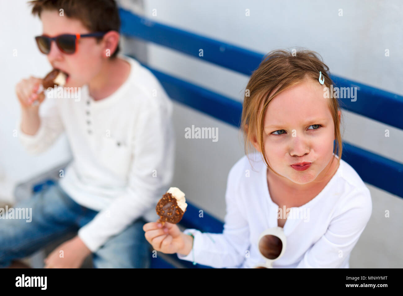 Two adorable kids eating ice cream outdoors on a hot summer day - Stock Image