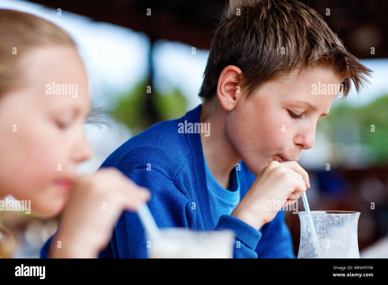 Kids brother and sister drinking milkshakes in outdoor cafe - Stock Image