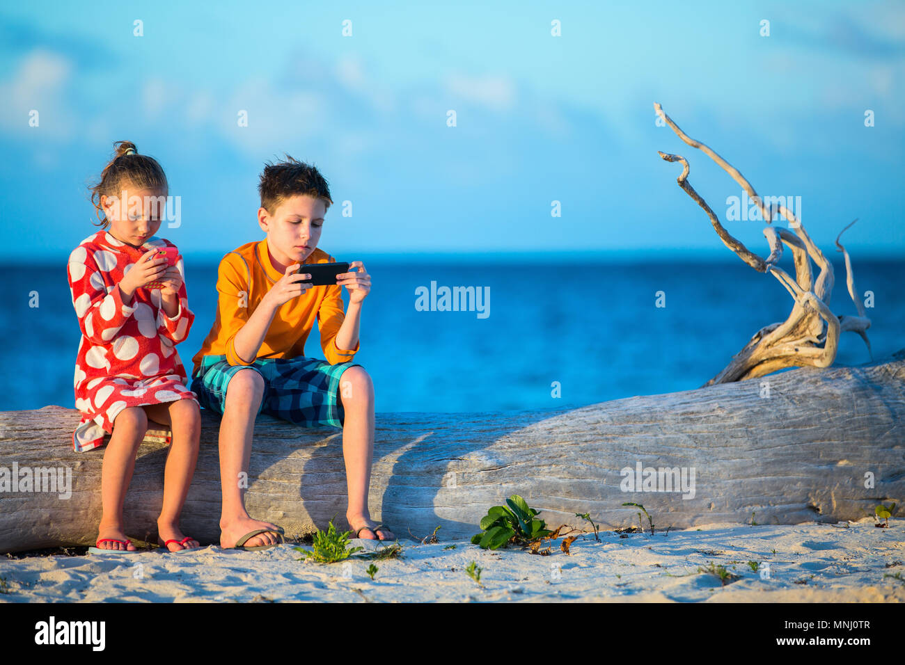 Kids playing on a portable game device or smartphone at beach - Stock Image