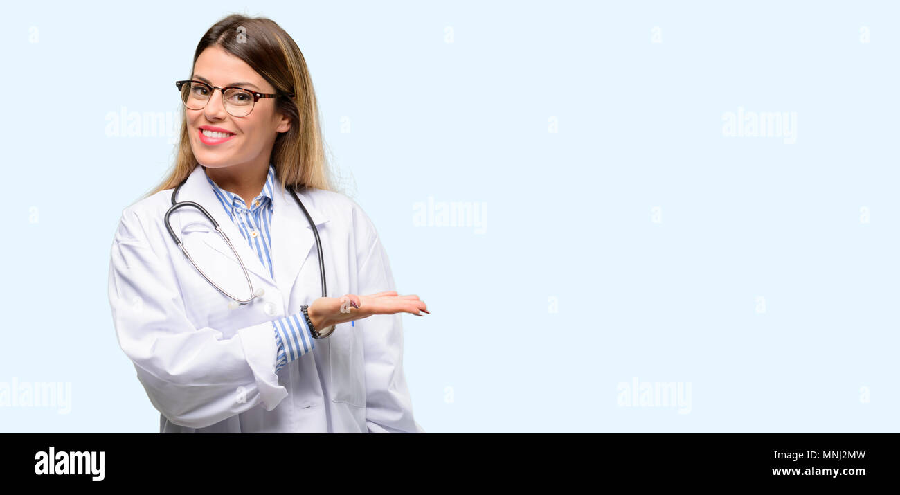 Young doctor woman, medical professional holding something in empty hand - Stock Image