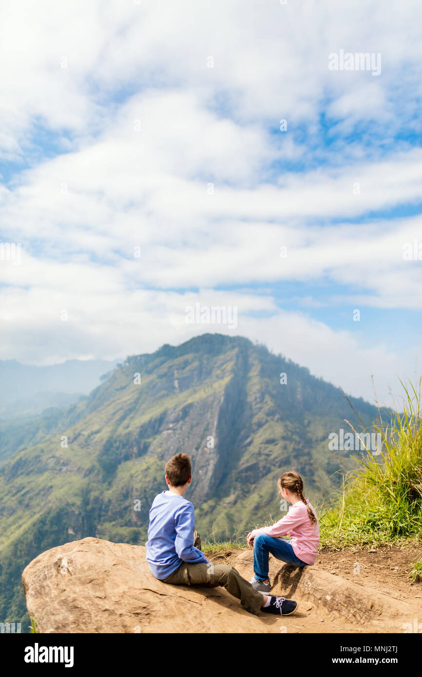 Kids enjoying breathtaking views over mountains and tea plantations from Little Adams peak in Ella Sri Lanka Stock Photo