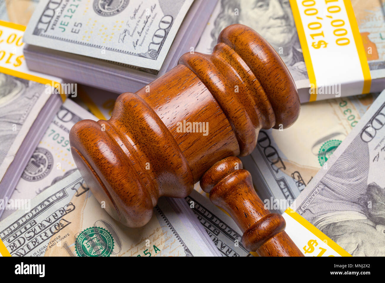 Pile of Hundred Dollar Bills with Judges Gavel on Top. - Stock Image