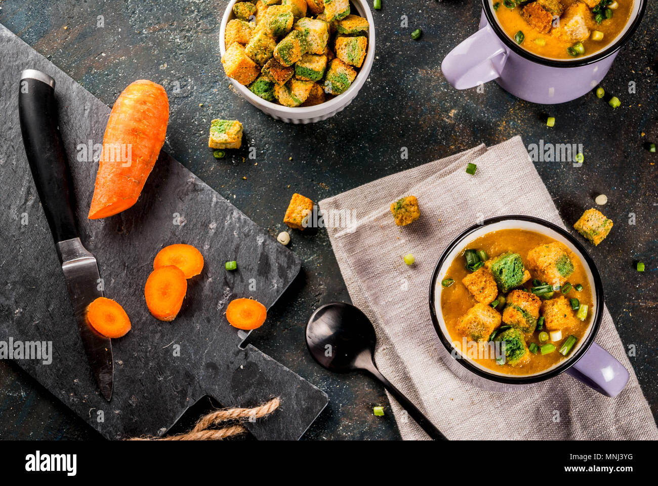 Homemade pureed carrot cream soup, with bread crackers, fresh herbs and cream. On a dark blue background, - Stock Image