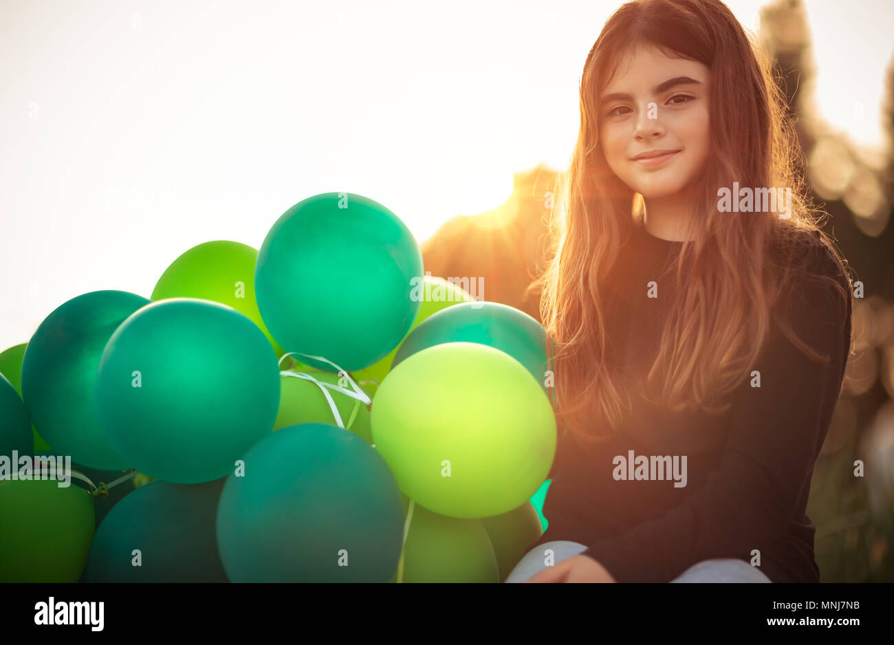 Portrait of a cute little girl sitting in the park with pile of green air balloons outdoors in mild evening sun light, celebrating birthday, preparati - Stock Image