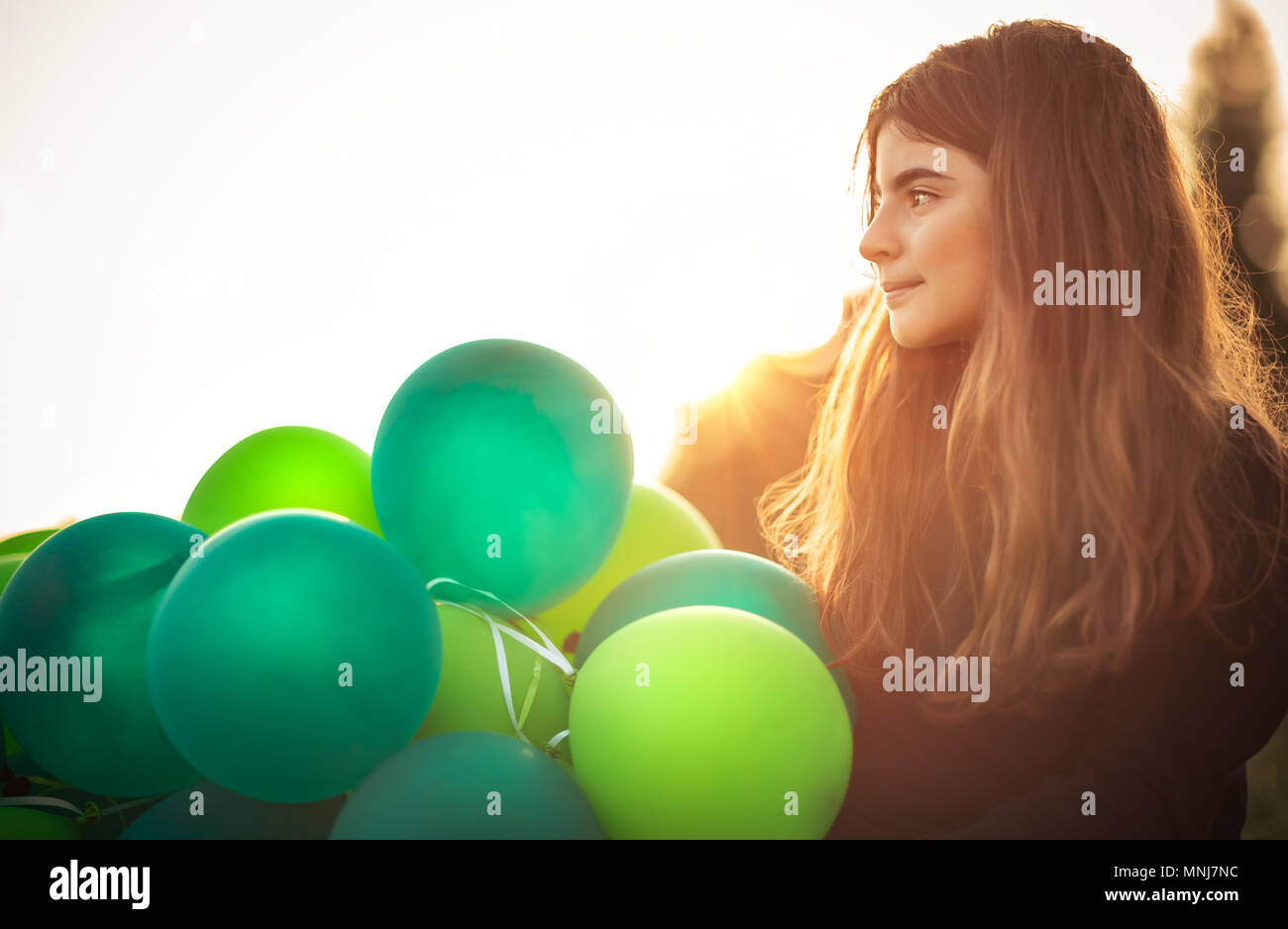 Portrait of a cute girl outdoors with big pile of green air balloons, preparing to celebrate birthday party, happy carefree childhood - Stock Image
