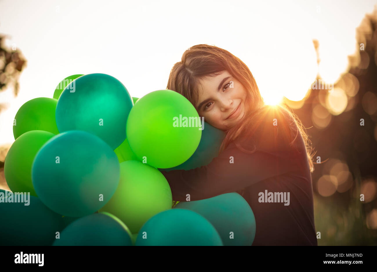 Portrait of a cute smiling girl outdoors hugging big pile of green air balloons, preparing to celebrate birthday party, happy carefree childhood - Stock Image