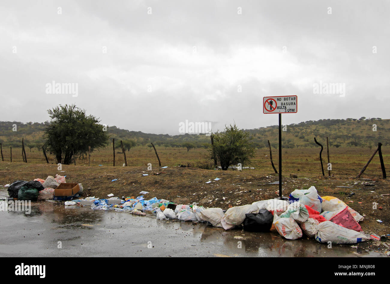Littering of garbage in front of do not litter sign, Chile - Stock Image