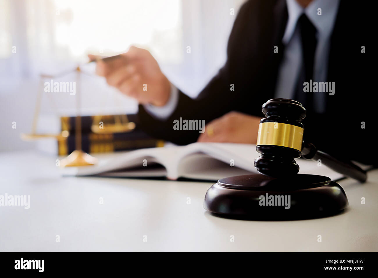 Justice and Law concept. Legal counsel presents to the client a signed contract with gavel and legal law or legal having team meeting at law firm - Stock Image