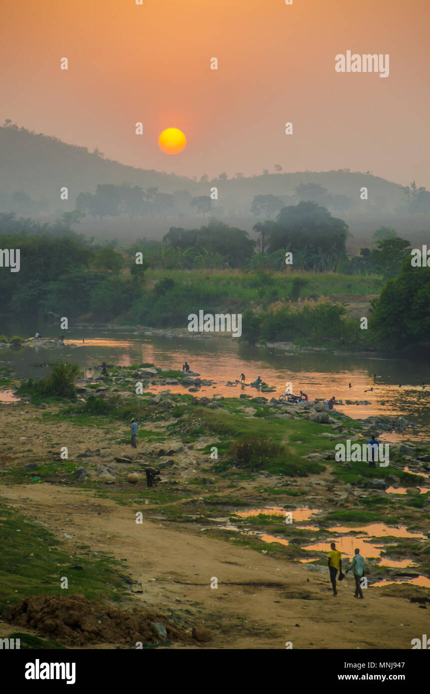 Foggy red sunset over river with African people walking and washing, Nigeria, Africa - Stock Image